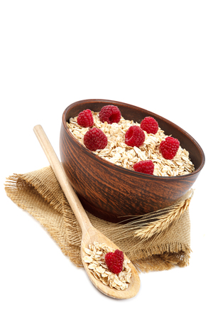 Oatmeal flakes and raspberries isolated on white background.