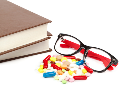 Stack of books and pills, capsules isolated on white background. Medicaments. Medicines and drugs. Banco de Imagens
