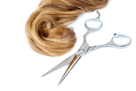 Professional hairdressing scissors and a lock of blond hair isolated on white background.