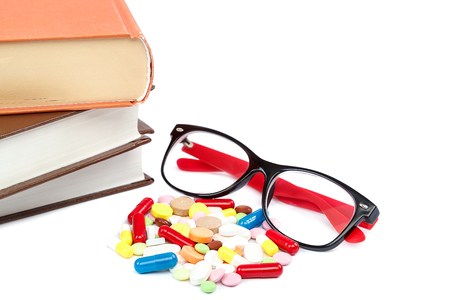 Stack of books and pills, capsules isolated on white background. Medicaments. Medicines and drugs. Stock Photo
