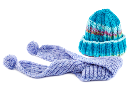 Blue knitted cap and scarf isolated on white background.
