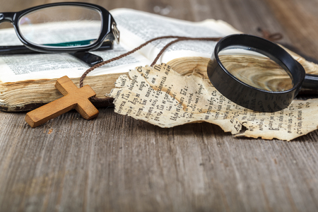 Ancient holy book of a wooden cross on a cord on a wooden background.