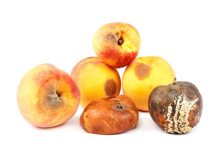 Frutos de una manzana y melocotón con podredumbre aislado sobre fondo blanco.