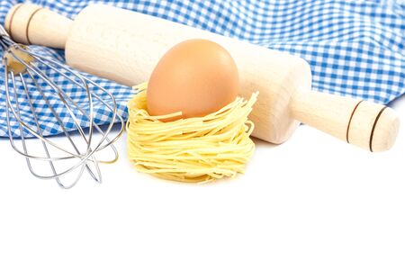 Flour, pasta, egg and cooking utensils isolated on a white background.