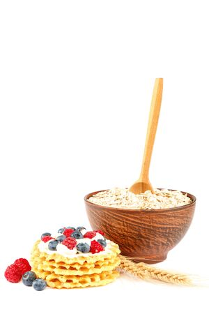 Fresh blueberries, raspberries, waffle cookies and oatmeal in a bowl with a wooden spoon isolated on a white background. Stockfoto