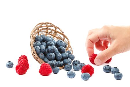 Fresh blueberries and raspberries in wicker baskets isolated on a white background.