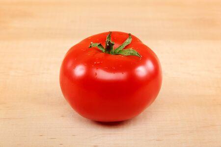 Fresh tomato fruit on wooden boards.