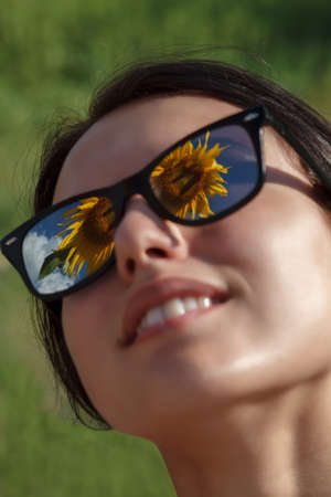 Beautiful girl with sunglasses in a field with sunflowers on a summer sunny day. Standard-Bild
