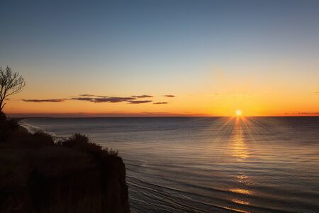 Calm sea, blue sky and bright sun at dawn. Sunset. 写真素材