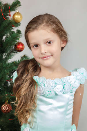 Lovely little girl with a Christmas tree isolated on a white background.