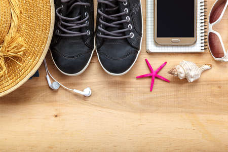 Travel accessories and clothes on wooden background.