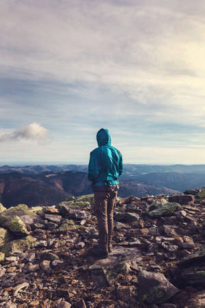 Young sad man traveler stands on top of a mountain.