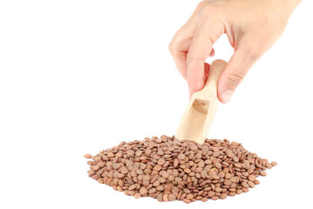 Lentil grains and a female hand with a wooden scoop isolated on a white background.