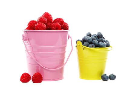 Fresh blueberries and raspberries in buckets isolated on a white background.