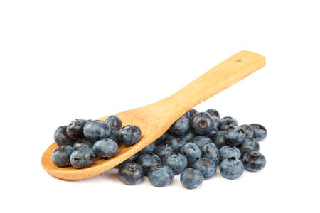 Fresh blueberries with a wooden spoon isolated on a white background.