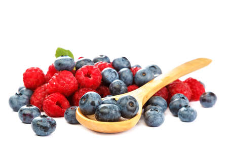Fresh blueberries and raspberries with a wooden spoon isolated on a white background.