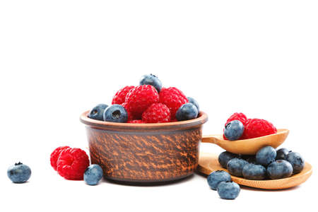 Fresh blueberries and raspberries in a bowl with a wooden spoon isolated on a white background. Standard-Bild