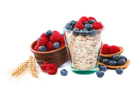 Fresh blueberries and raspberries, oatmeal in a bowl with a wooden spoon isolated on a white background.