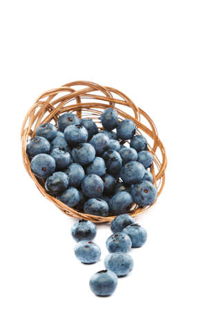 Fresh blueberries in a wicker basket isolated on a white background.