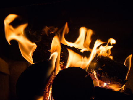 Burning wood and flames in a fireplace on a black background Stock Photo