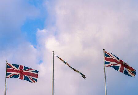 flagpoles: Three Union Jack flags flying in Trafalgar Square London. Stock Photo