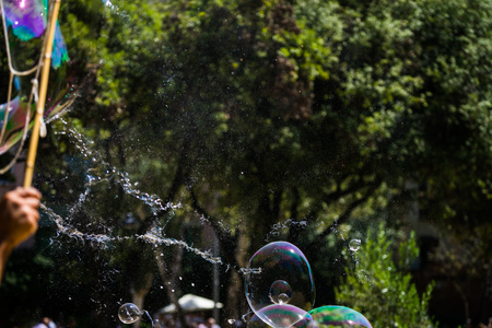 busker: A big bubble bursting in a park in Barcelona. Stock Photo