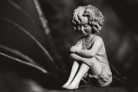 A garden fairy sitting in a tree.
