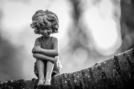 A fairy statue alone sitting in a tree.