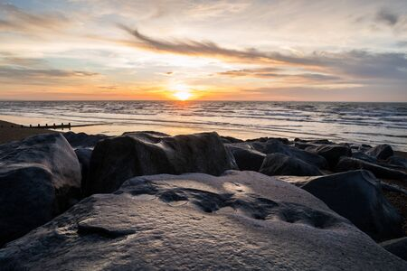 Looking over some large boulders at the sunrise in Brighton. Reklamní fotografie