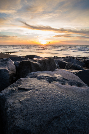 A line of boulders on Brighton beach at sunrise.