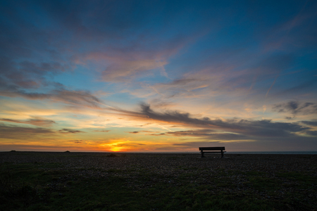 Brighton beach with a bench in foreground at sunrise.