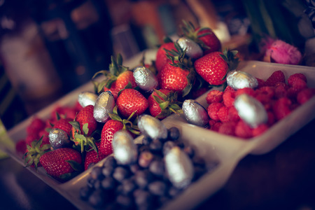 A selection of berries at Easter on a dining table with mini easter eggs dotted about.