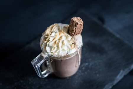 A hot chocolate with chocolate stick and glitter shot on slate, blurred shallow focus.