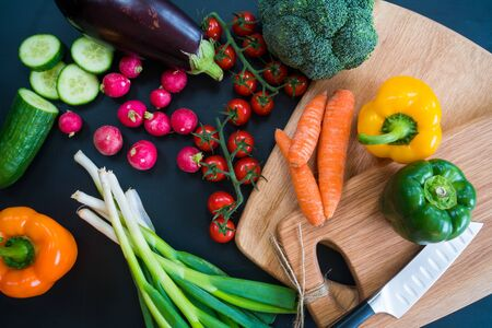 An overhead shot of various vegetables on chopping boards.