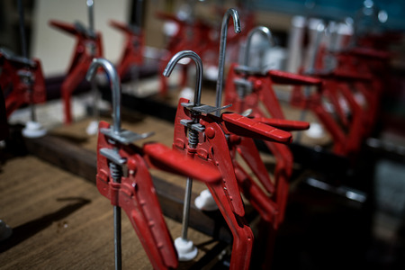 A row of red clamps in a workshop, shallow focus. Reklamní fotografie