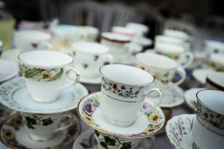 A stack of china tea cups with blurred background.