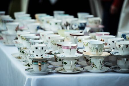 A table full of china tea cups with blurred background.