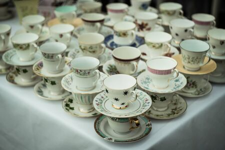 An overview of a table of tea cups at afternoon tea.