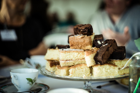 A plate of cakes at afternoon tea with blurred background.