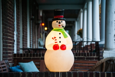 Photograph of a Lighted Christmas Snowman Decoration on the front porch of a row home in Baltimore City.