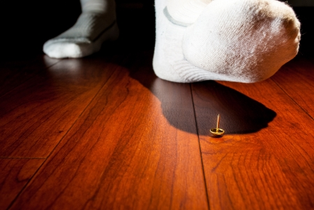 Photograph of a human foot about to step on an upright tack on a wooden floor.