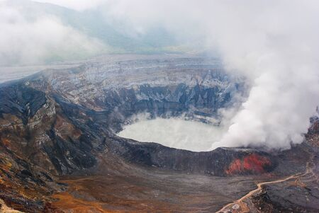 View of the caldera of the Costa Rican volcano known as Poas.  Steam is rising up from the discolored crater and gray lake. Фото со стока
