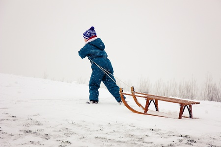 to go sledding: boy pulling his sleigh up the hill