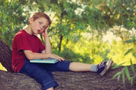 niños estudiando: Little boy pensando en lo que había leído Foto de archivo