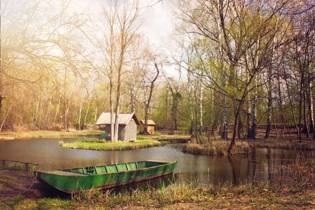 fishing cabin: Sunlit pond with fishing boat