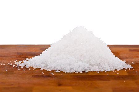 sel: fleur de sel, white sea salt crystals on wooden table, white background Stock Photo