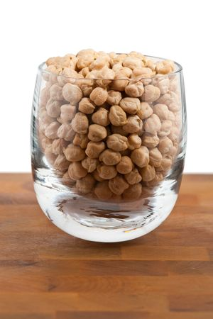 Chickpeas in Glass on wooden table, white background photo