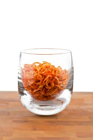 hotness: dried chopped red chilies in glass, white background