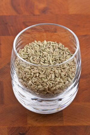 dried fennel seeds in glass on wooden table photo