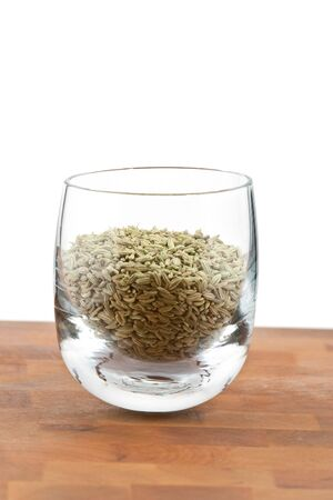 dried fennel seeds in glass on wooden table, white background photo